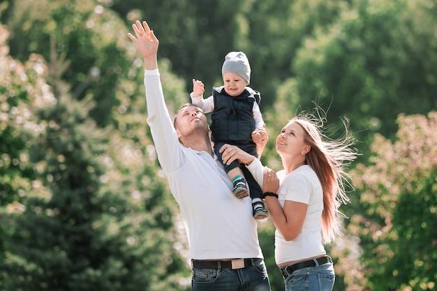 Família feliz com um filho pequeno no fundo de um parque de verão