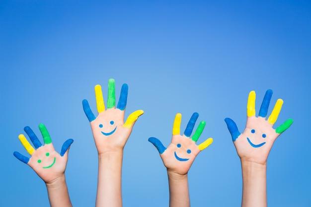 Família feliz com um smiley nas mãos contra o fundo do céu azul de verão