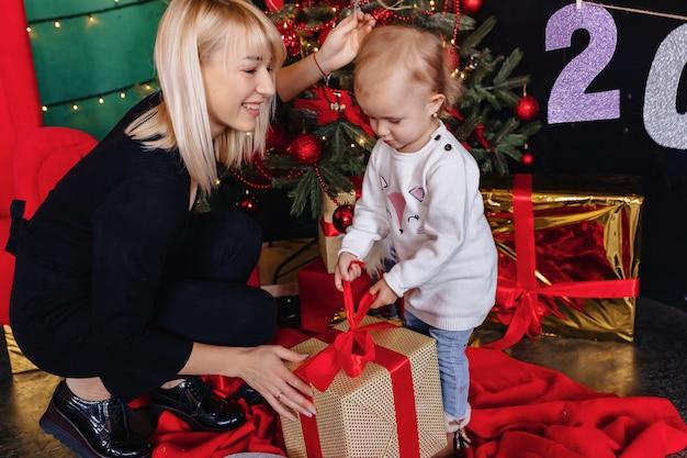 Família feliz com uma criança comemorar o ano novo perto da árvore de natal