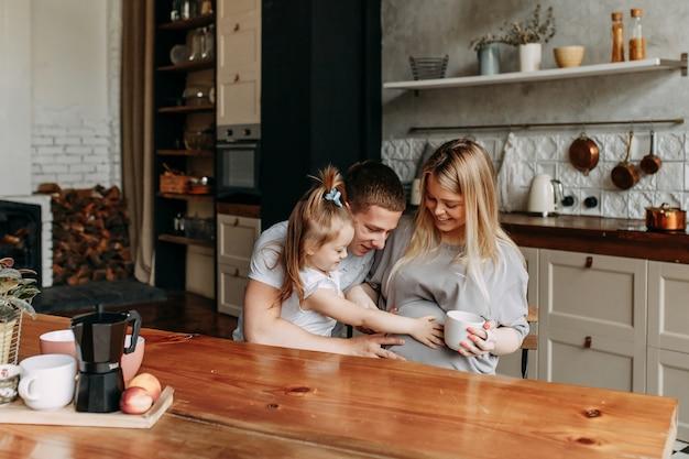 Família feliz com uma criança cozinha e ri na cozinha