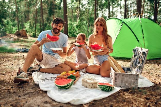 Família feliz com uma criança em um piquenique sentar em um cobertor perto da tenda e comer comida frita e melancia durante o fim de semana na floresta. acampar, recreação, caminhadas.