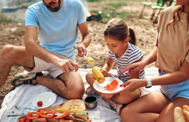 Família feliz com uma criança em um piquenique, sentar na colcha e comer comida frita no fogo durante o fim de semana. acampar, recreação, caminhadas.