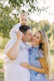 Família feliz com uma criança pequena. o garoto senta no pescoço do pai e o pai beija a mãe na bochecha. jovem mãe é feliz e sorridente