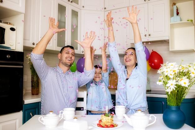 Família feliz comemora aniversário em casa na cozinha