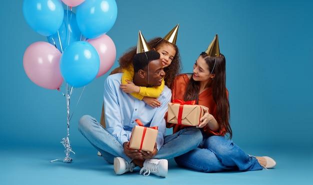 Família feliz comemora aniversário, fundo azul. menina e os pais de bonés soprando apitos de festa, balões e decoração de confetes