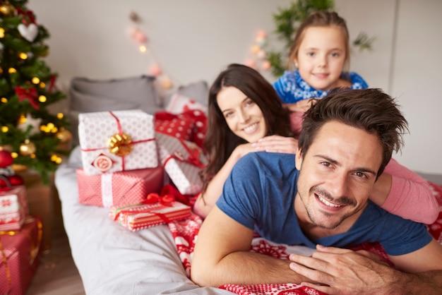 Família feliz comemorando o natal na cama