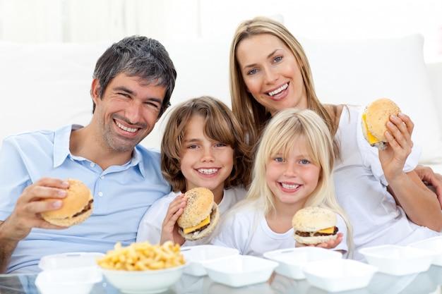 Família feliz comendo hambúrgueres sentados no chão