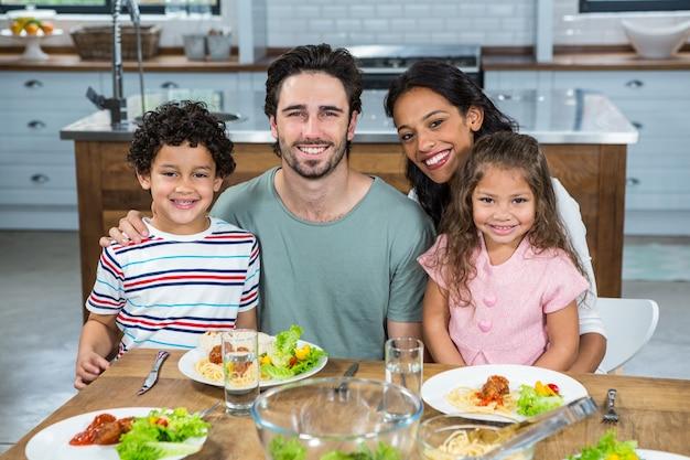 Família feliz comendo juntos na cozinha