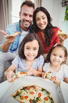 Família feliz comendo pizza em casa