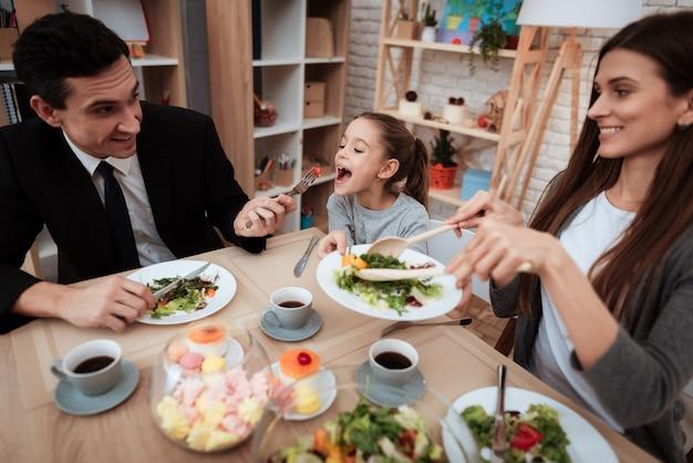 Família feliz comendo pratos na mesa juntos