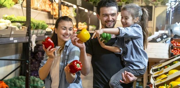 Família feliz compra legumes. família alegre de três escolhendo tomates no departamento de vegetais de supermercado ou mercado.