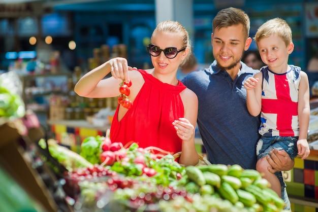 Família feliz compra legumes