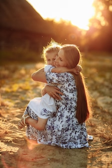 Família feliz. conceito de dia das mães mãe, brincando com sua filhinha de bebê na luz do sol dia de verão. bela luz do sol no parque.