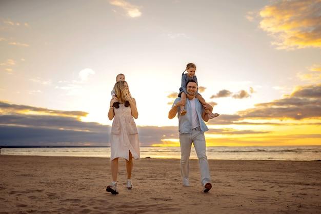 Família feliz correndo ao longo da praia no pôr do sol. linda jovem mãe carregando sua filha nos ombros, o pai de óculos carrega seu filho bebê. foto de alta qualidade