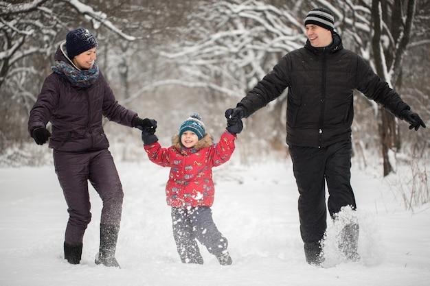 Família feliz correndo na neve no inverno