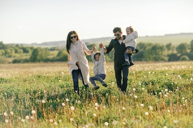 Família feliz correndo pelo campo. pai, mãe e duas filhas.