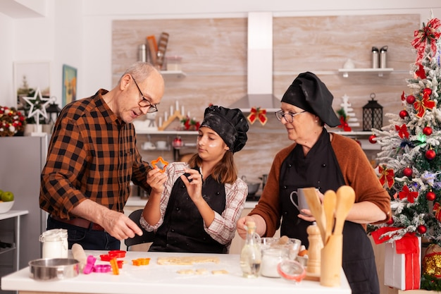 Família feliz cozinhando tradicional sobremesa de pão de gengibre fazendo massa caseira