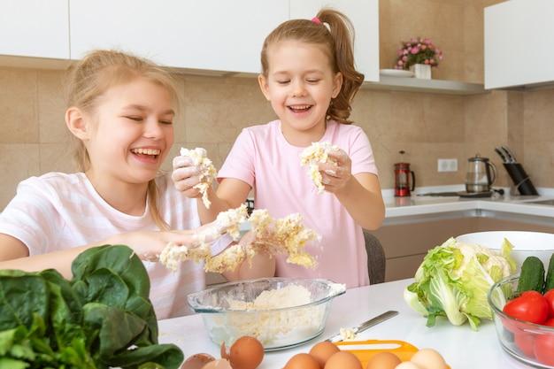 Família feliz crianças engraçadas estão preparando a massa, assar biscoitos na cozinha. irmãs se divertindo juntos rindo