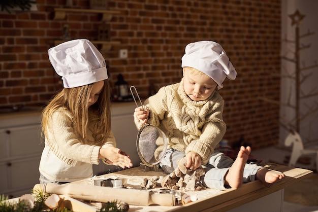 Família feliz crianças engraçadas estão preparando a massa, jogando com farinha na cozinha