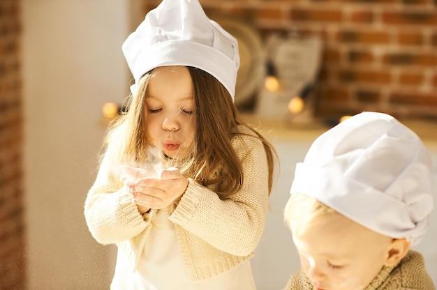 Família feliz crianças engraçadas estão preparando a massa