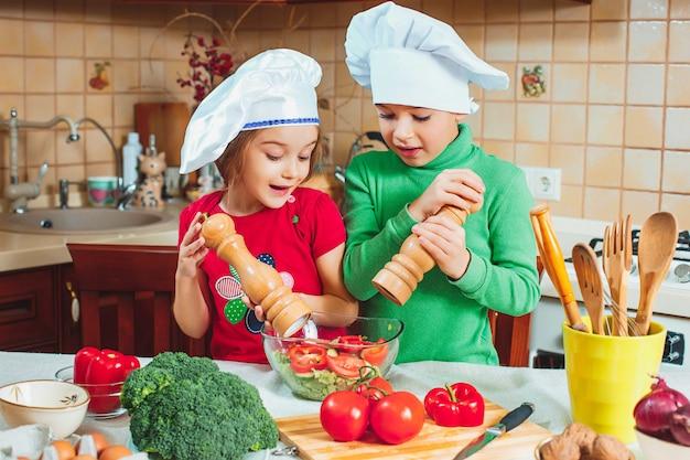 Família feliz crianças engraçadas estão preparando uma salada de legumes frescos na cozinha