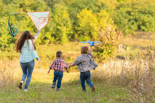 Família feliz da jovem mãe e seus filhos, lançando uma pipa na natureza