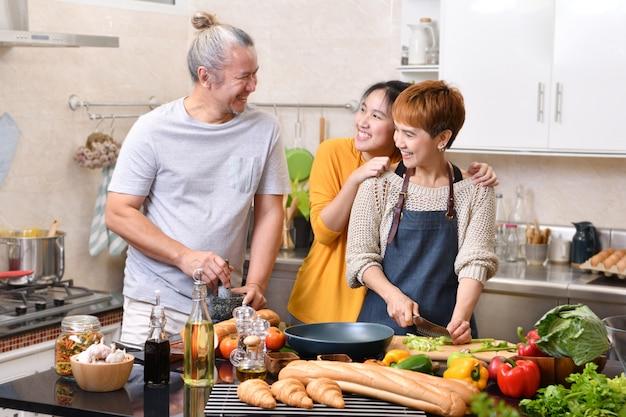 Família feliz da mãe pai e filha cozinhando na cozinha, fazendo comida saudável, se divertindo