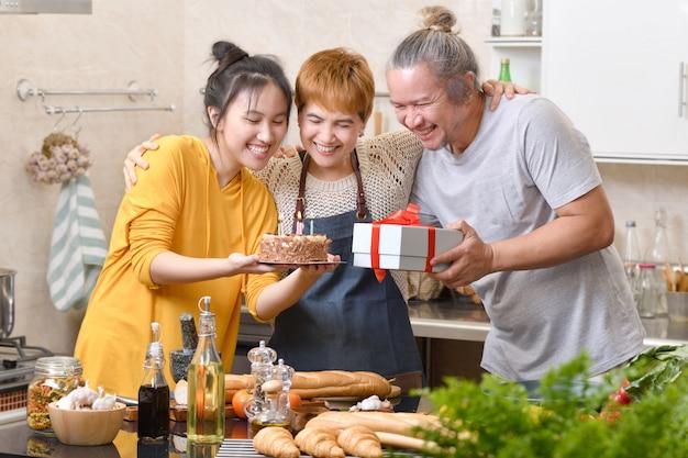 Família feliz da mãe pai e filha na cozinha comemorando a festa de aniversário com bolo e presente