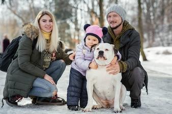 Família feliz da mãe, pai e filha posar com bulldogs americanos no parque