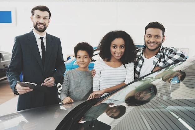 Família feliz da raça misturada e agente perto do automóvel novo.