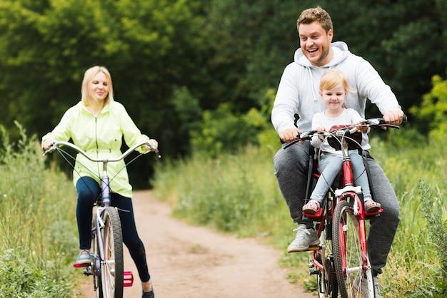 Família feliz da vista dianteira em bicicletas