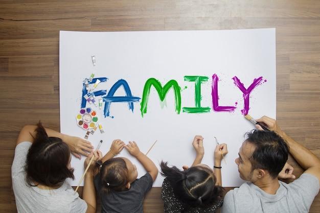 Família feliz da vista superior que encontra-se no assoalho com pintura usando aquarelas