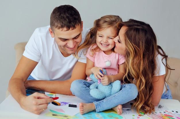 Família feliz de aparência europeia. sorrindo pais jogar e aprender a desenhar sua menina bonitinha. um homem e uma mulher bonita com uma criança se divertir.