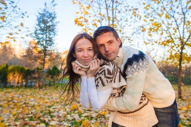 Família feliz de dois andando no parque do outono em um dia ensolarado de outono