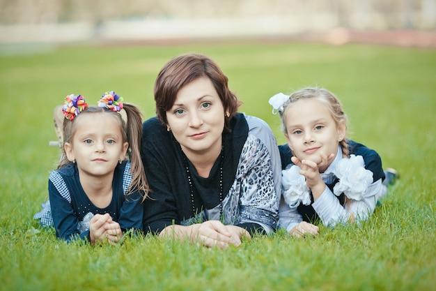Família feliz de mãe e duas filhas ao ar livre na grama em um parque com rostos sorridentes, todos deitados se divertindo