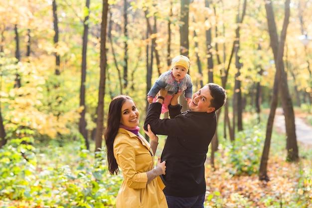 Família feliz de mãe, pai e bebê na natureza do outono