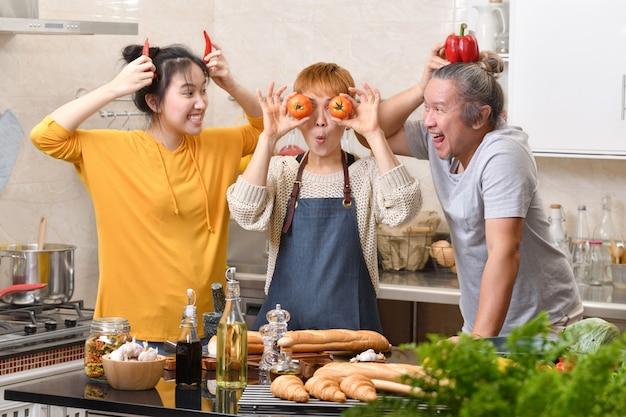 Família feliz de mãe pai e filha cozinhando na cozinha, fazendo comida saudável juntos, se divertindo e fazendo caretas