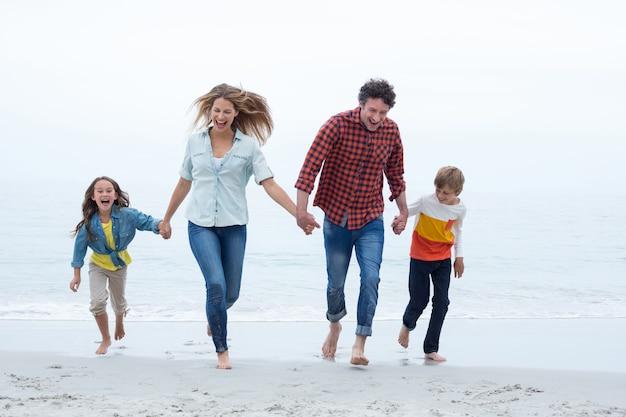 Família feliz, de mãos dadas enquanto corre na costa do mar