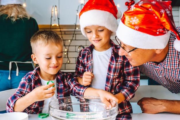 Família feliz de pai e dois filhos filhos gêmeos assar biscoitos na cozinha antes do natal.