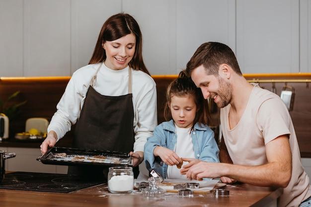 Família feliz de pai e mãe com filha cozinhando juntos