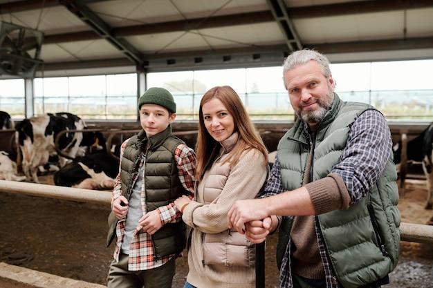 Família feliz de pai, mãe e filho adolescente em trajes de trabalho em frente à câmera contra grandes cercados com vacas leiteiras de raça pura