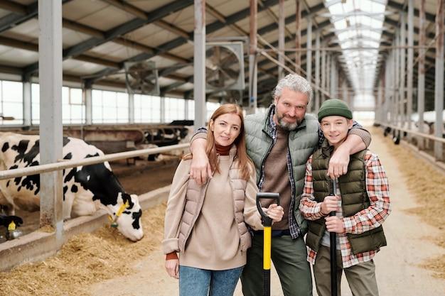 Família feliz de pai, mãe e filho adolescente em trajes de trabalho em frente à câmera contra o longo corredor entre os piquetes com o gado