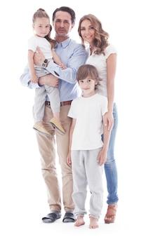 Família feliz de pais e dois filhos isolados no fundo branco