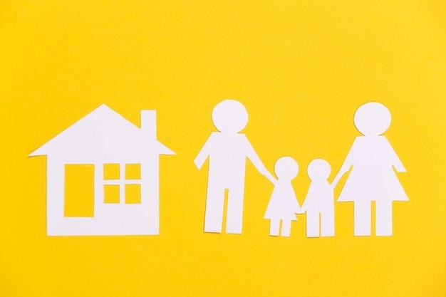 Família feliz de papel com casa em amarelo