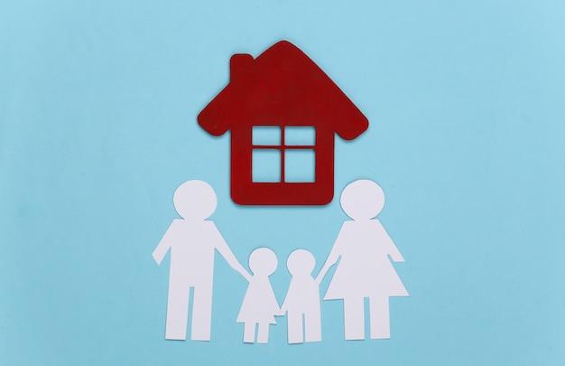 Família feliz de papel com casa em azul