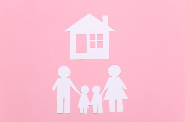 Família feliz de papel com casa em pastel rosa