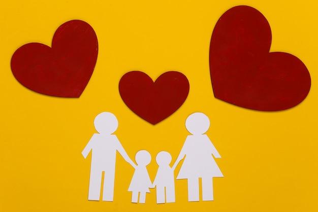 Família feliz de papel junto com corações vermelhos em amarelo