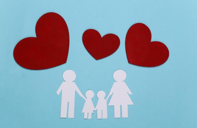 Família feliz de papel junto com corações vermelhos em azul