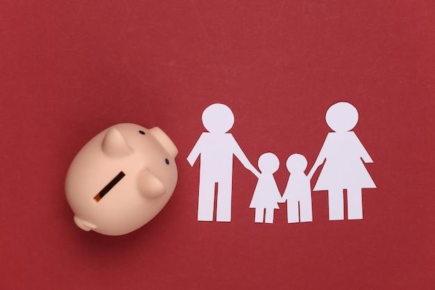 Família feliz de papel junto com o cofrinho no vermelho. orçamento familiar