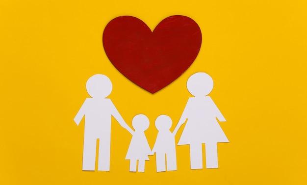 Família feliz de papel junto com um coração vermelho em amarelo